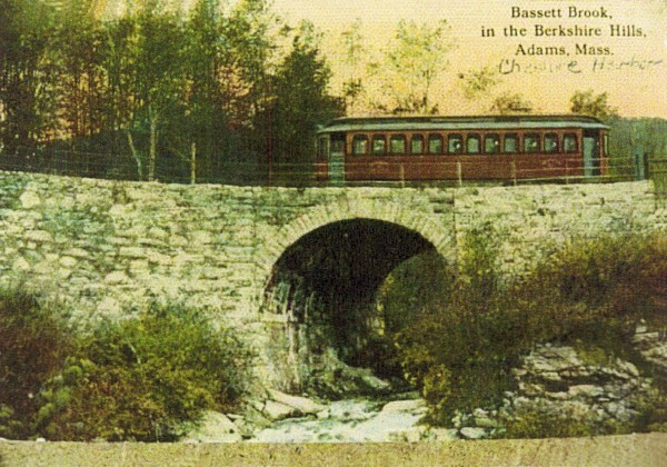 Trolley car on top of a stone bridge in the woods